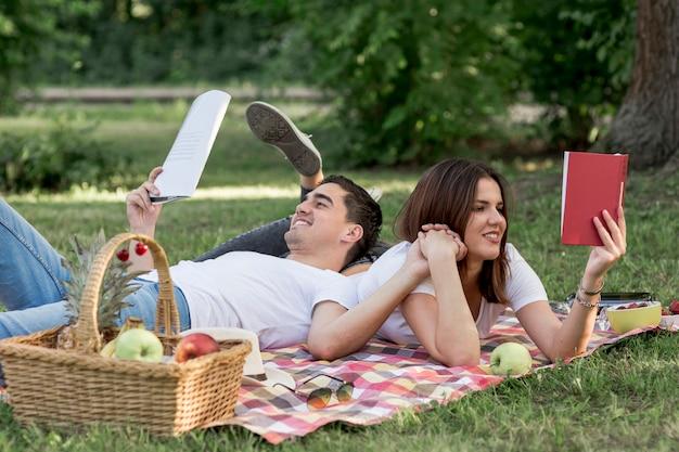 Giovani coppie che leggono libri in natura