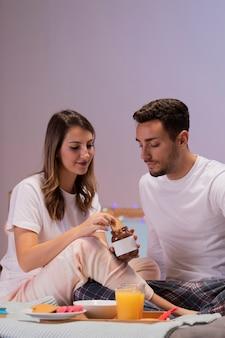 Giovani coppie che mangiano i dolci a letto