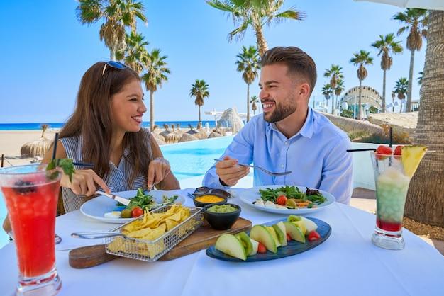 Giovani coppie che mangiano in un ristorante in piscina