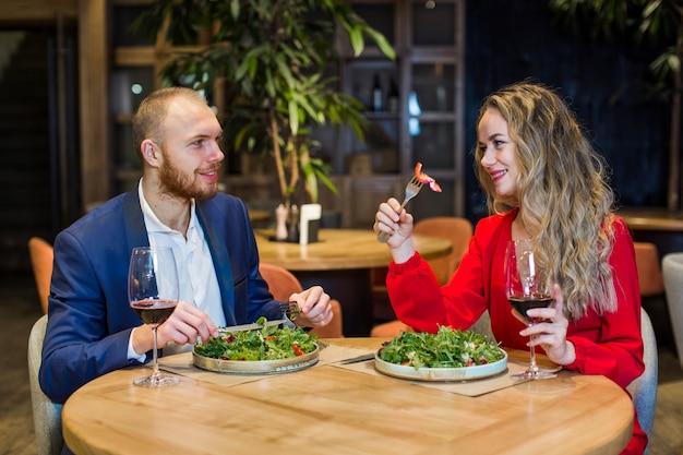 Giovani coppie che mangiano insalata nel ristorante