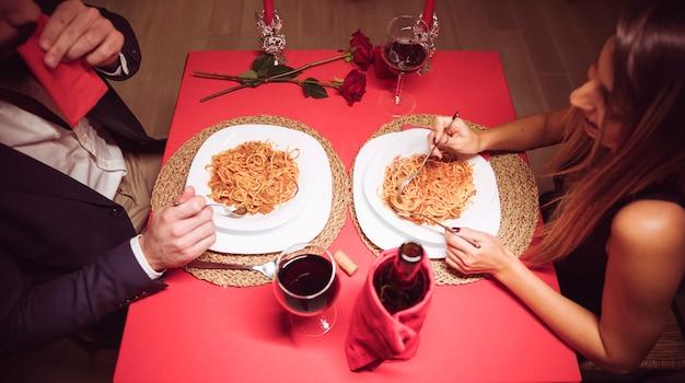Giovani coppie che mangiano pasta al tavolo festivo