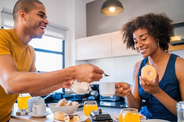 Giovani coppie che mangiano prima colazione a casa.