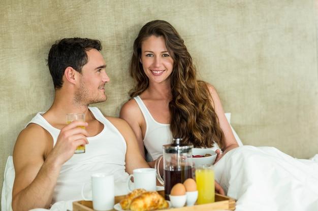 Giovani coppie che mangiano prima colazione sul letto in camera da letto