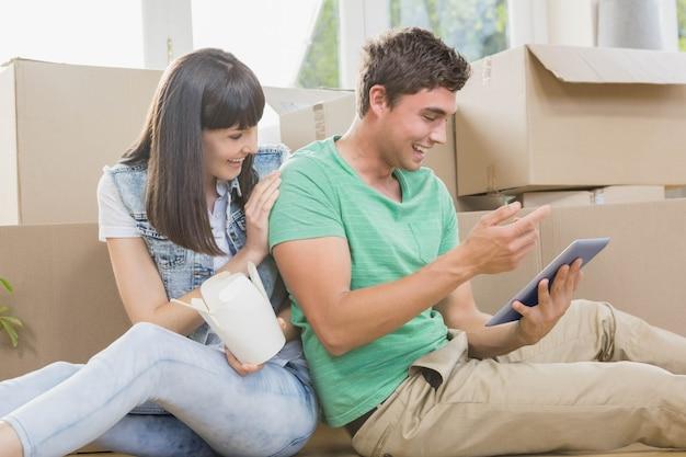 Giovani coppie che mangiano tagliatella e che utilizzano compressa digitale nella loro nuova casa