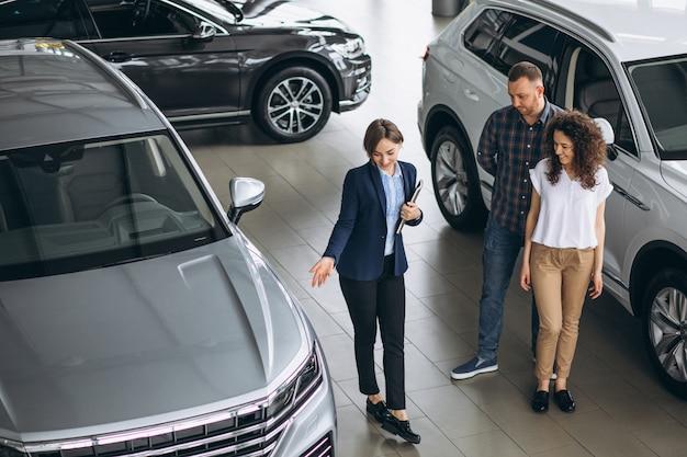 Giovani coppie che parlano con un venditore in una sala d'esposizione dell'automobile