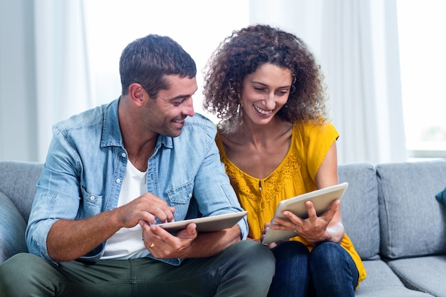 Giovani coppie che per mezzo di una compressa digitale sul sofà