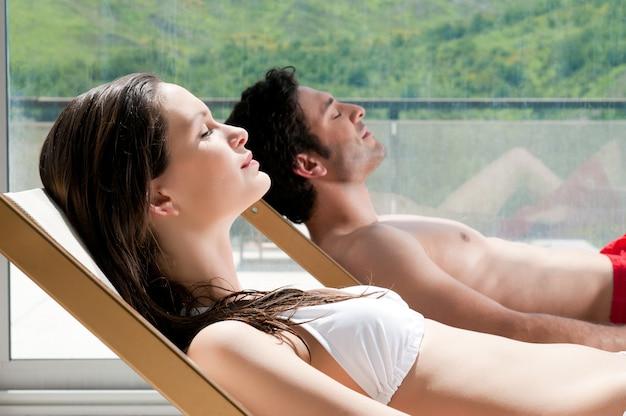 Giovani coppie che prendono il sole insieme sulle sedie a sdraio