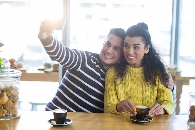 Giovani coppie che prendono selfie in self-service
