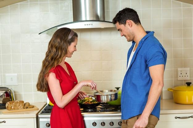 Giovani coppie che preparano insieme alimento nella cucina a casa
