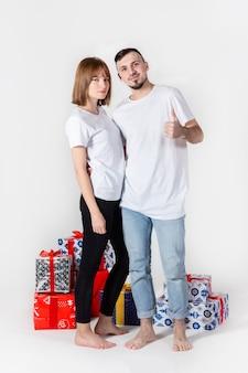 Giovani coppie che propongono con i regali di natale