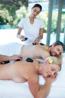 Giovani coppie che ricevono un massaggio con pietre calde dal massaggiatore
