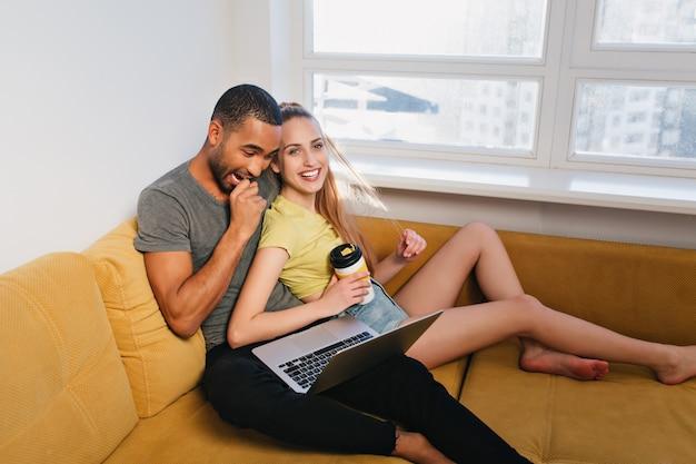 Giovani coppie che ridono e che esaminano il computer portatile. l'uomo ha visto qualcosa di divertente e ha riso davvero. gli amanti trascorrono il tempo libero su un divano in una stanza luminosa. coppia abbracciati e divertiti con i vestiti di casa.
