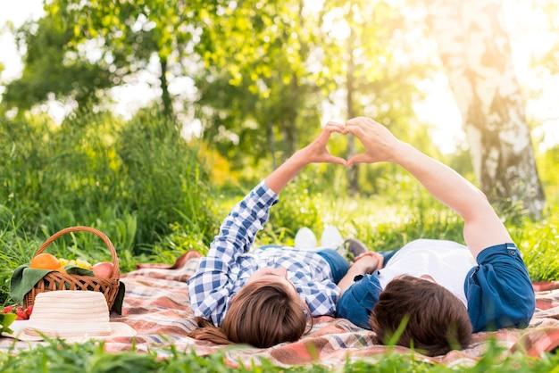 Giovani coppie che riposa sul plaid e mostrando il gesto del cuore