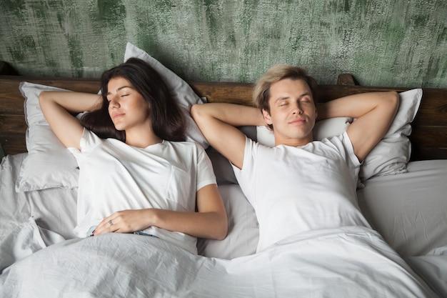 Giovani coppie che riposano dormendo bene insieme nel letto comodo