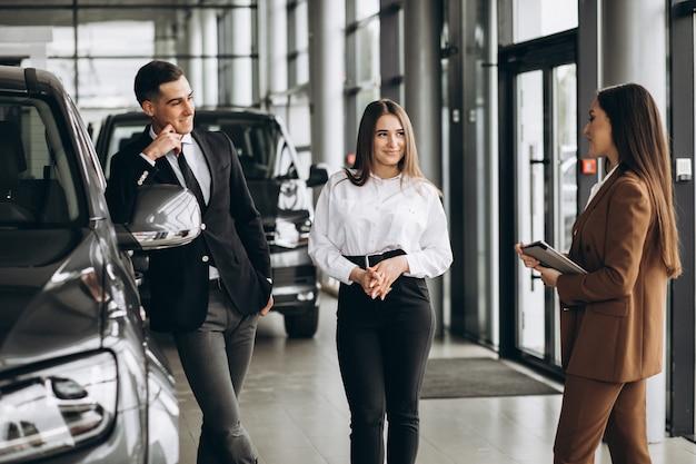 Giovani coppie che scelgono un'automobile in una sala d'esposizione dell'automobile