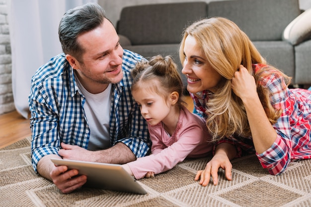 Giovani coppie che se lo esaminano mentre figlia che per mezzo della compressa digitale