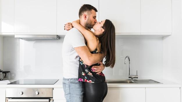 Giovani coppie che si amano che abbracciano nella cucina