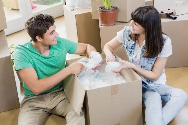 Giovani coppie che si assistono mentre disimballando i contenitori di cartone in nuova casa