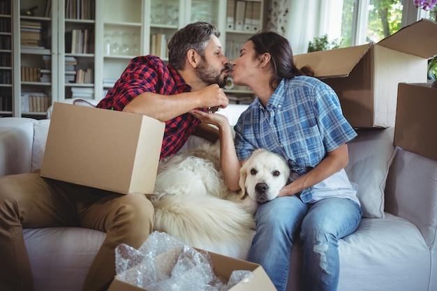Giovani coppie che si baciano mentre disimballano i contenitori di cartone