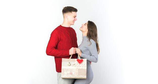 Giovani coppie che si levano in piedi con il sacchetto del regalo