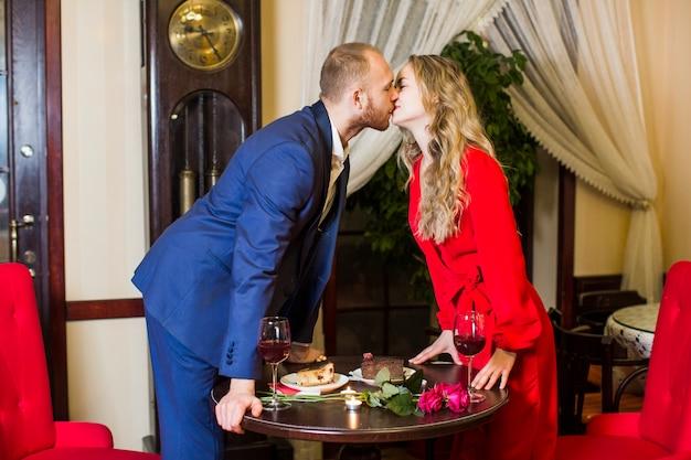 Giovani coppie che si levano in piedi e che baciano nel ristorante