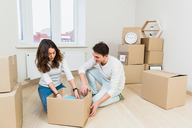 Giovani coppie che si muovono verso il nuovo posto che si siede vicino alla scatola di cartone che disimballa i piatti