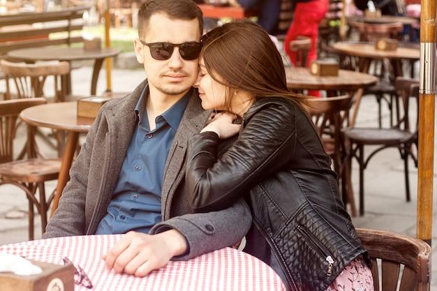 Giovani coppie che si siedono al caffè della via che ha appuntamento romantico.