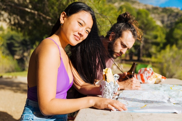 Giovani coppie che si siedono alla tabella con la mappa e spuntino