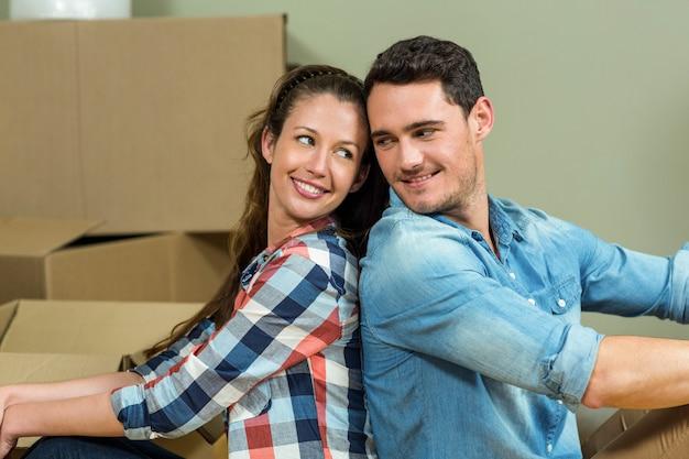 Giovani coppie che si siedono di nuovo alla parte posteriore e che si esaminano nella loro nuova casa