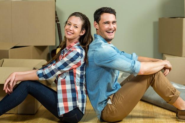 Giovani coppie che si siedono di nuovo alla parte posteriore e che sorridono nella loro nuova casa