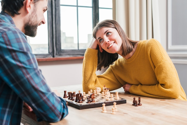 Giovani coppie che si siedono insieme giocando gli scacchi a casa