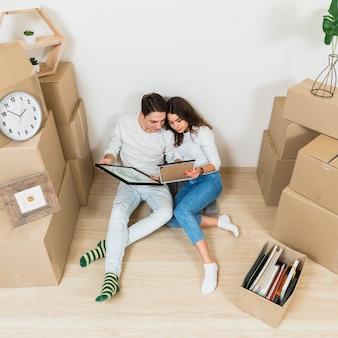 Giovani coppie che si siedono insieme guardando la cornice nel loro nuovo appartamento