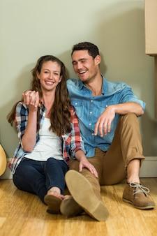 Giovani coppie che si siedono insieme sul pavimento e che sorridono nella loro nuova casa