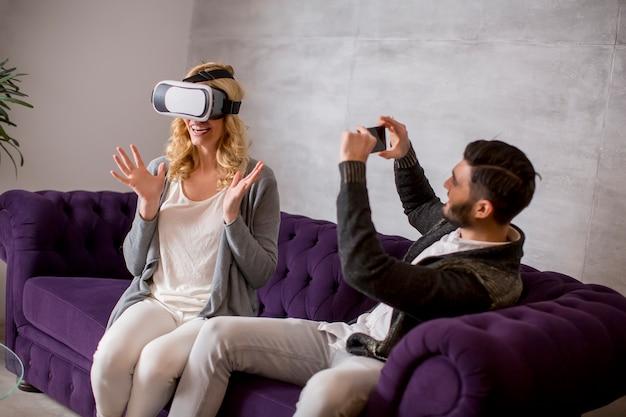 Giovani coppie che si siedono nella stanza mentre la giovane donna ha i vetri di una realtà virtuale