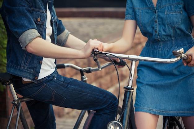 Giovani coppie che si siedono su una bicicletta di fronte alla città