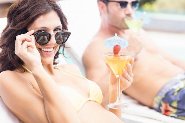 Giovani coppie che si siedono sui lettini dalla piscina