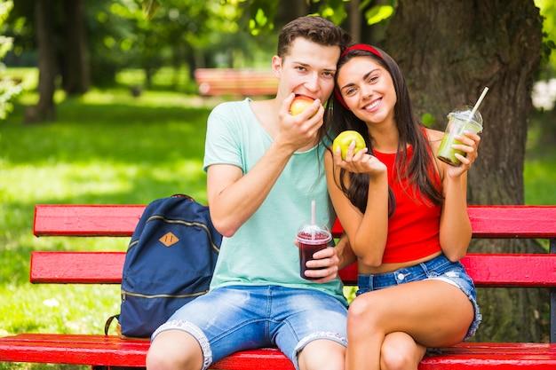 Giovani coppie che si siedono sul banco che tiene alimento sano e frullati nel parco