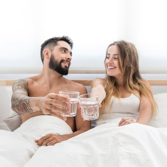 Giovani coppie che si siedono sul letto che tosta bicchiere d'acqua