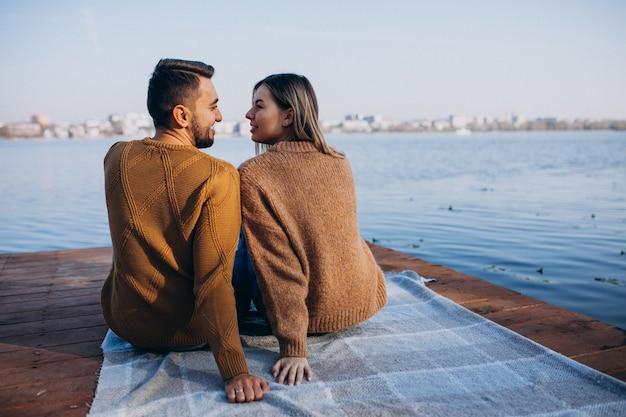 Giovani coppie che si siedono sul ponte della piattaforma dal fiume