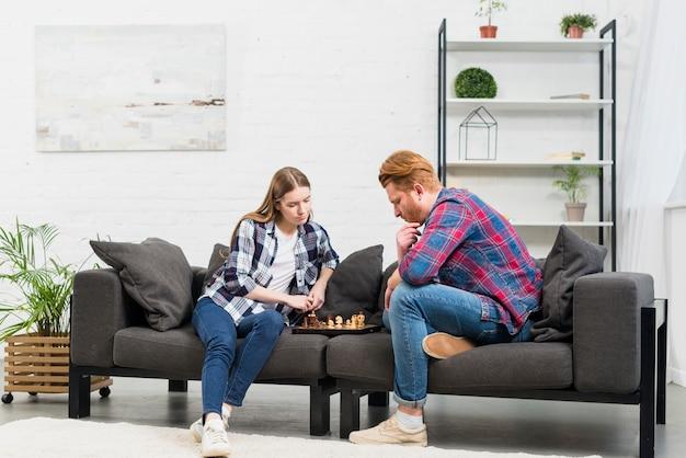 Giovani coppie che si siedono sul sofà che gioca il gioco di scacchi nel salone