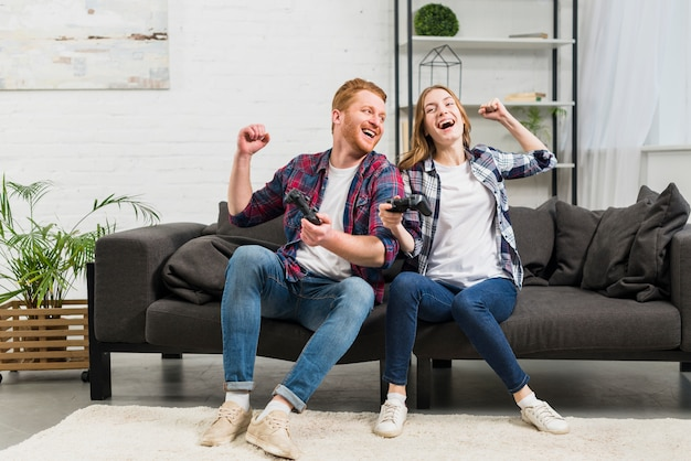 Giovani coppie che si siedono sul sofà che gioca il video gioco nel salone