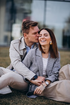Giovani coppie che si siedono sull'erba dalla costruzione
