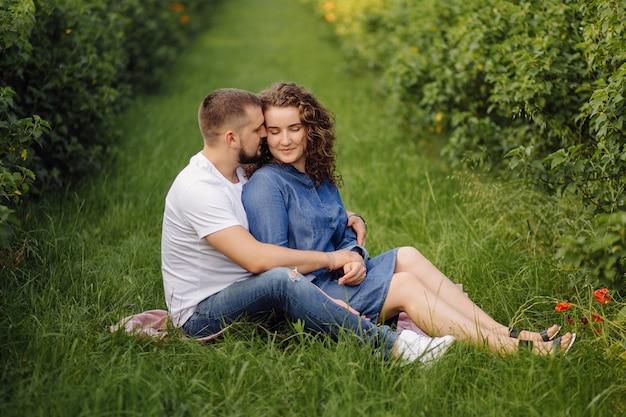 Giovani coppie che si siedono sull'erba e sul rilassamento
