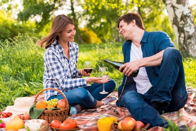 Giovani coppie che si siedono sulla coperta e sul vino di versamento