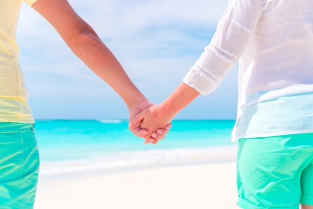 Giovani coppie che si tengono per mano alla spiaggia tropicale