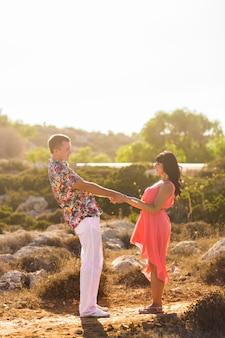 Giovani coppie che si tengono per mano e che se esaminano il giorno di estate soleggiato.
