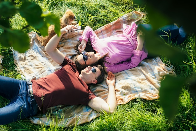 Giovani coppie che si trovano sul prato testa a testa nel parco. vista dall'alto