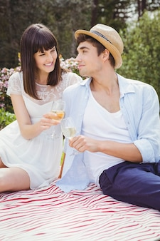 Giovani coppie che sorridono e che mangiano bicchiere di vino in giardino