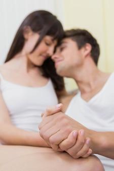 Giovani coppie che sorridono e che si stringono a sé sul sofà in salone