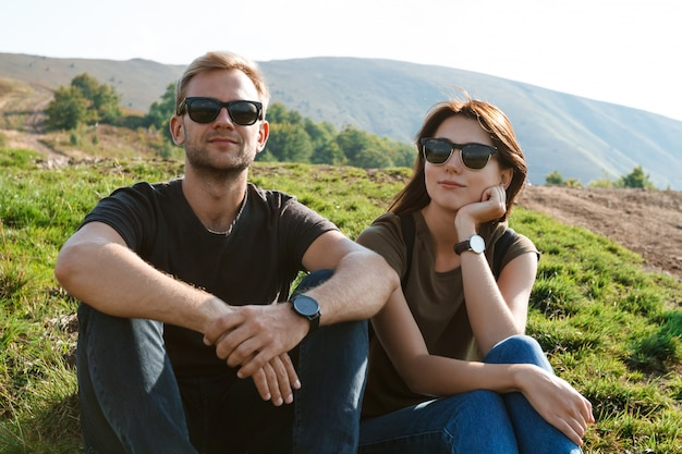 Giovani coppie che sorridono, godendo del lanscape delle montagne, sedentesi sulla collina
